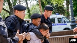 Kazakh policemen detain an opposition activist during a rally in Almaty in June 2018.