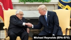 President Donald J. Trump shakes hands with former Secretary of State Henry Kissinger during their meeting in the Oval Office of the White House, in Washington, DC, 10 October 2017.
