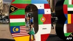 Ребенок есть мороженое, сидя внутри скульптурной композиции, установленной на площади в Приштине. 3 апреля 2013 года.