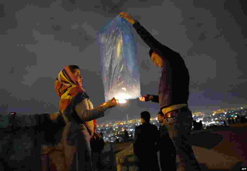 An Iranian couple lights a lantern in a park in Tehran as part of festivities ahead of the annual spring festival of Norouz. (AFP)