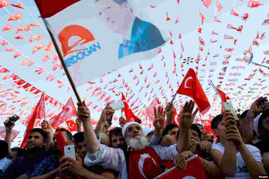 People wave national flags as they wait for the arrival of Turkey's President Recep Tayyip Erdogan at a rally in Gaziantep. (Reuters/Umit Bektas)