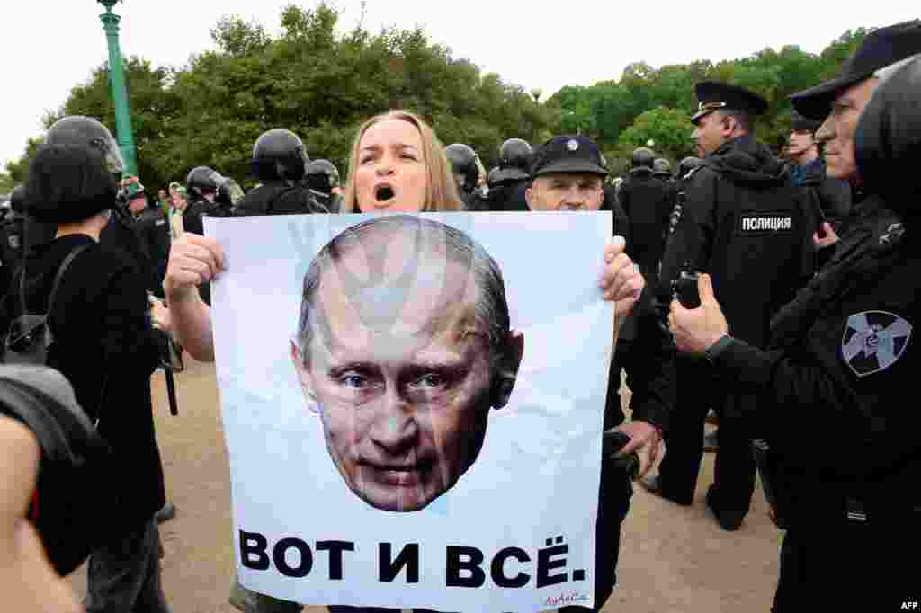 """A woman holds a poster bearing a portrait of Russian President Vladimir Putin and reading, """"That's All"""" during an unauthorized opposition rally in the center of St. Petersburg on June 12. Some 1,150 people were detained at rallies across the country. (AFP/Olga Maltseva)"""