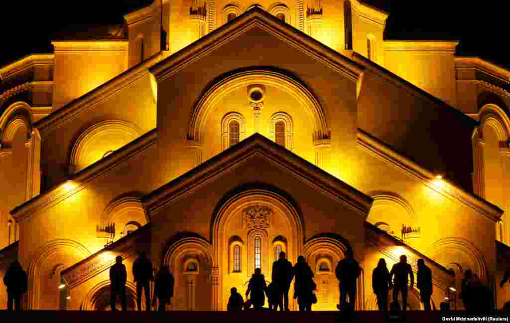 People stand before the Holy Trinity Cathedral during a midnight Christmas service in Tbilisi, Georgia, on January 7. (Reuters/David Mdzinarishvili)