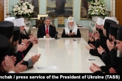 Ukrainian President Petro Poroshenko (center left) and Patriarch Filaret (center right) meet with members of the clergy of the Ukrainian Orthodox Church in Kyiv on October 21.