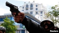 Пророссийский активист направил пистолет на сторонников украинских властей во время столкновений на улицах Одессы. 2 мая 2014 года.