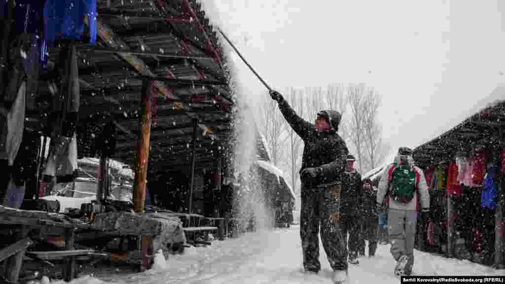 Продавец на местном рынке сбивает снег с крыши своей палатки
