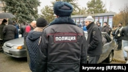 Российский полицейский наблюдает за тем, как крымские активисты встречают адвоката Эмиля Курбединова после выхода из ИВС. Симферополь, 11 декабря 2018 года