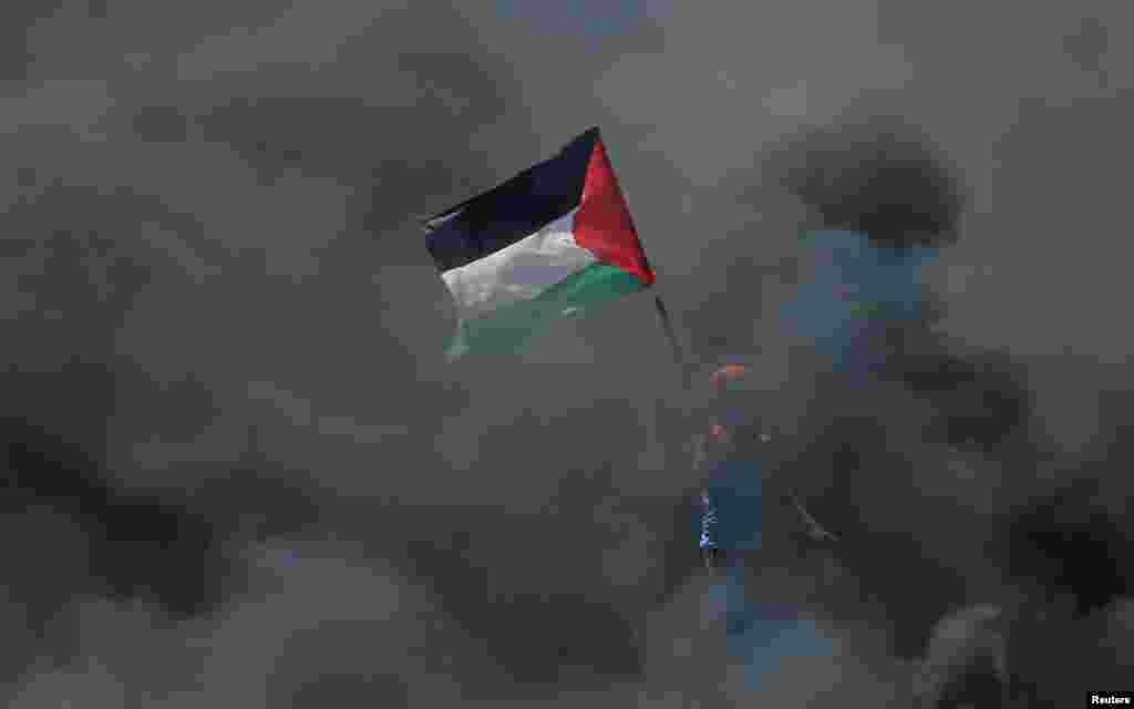 Палестинец в дыму от горящих покрышек протестует против переноса американского посольства в Иерусалим.