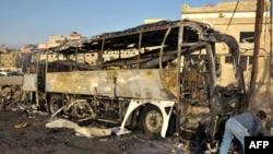 Сирия -- Дамасктын чет жакасында сириялык жигит күйүп кеткен автобустун бомба коюлган жерин кароодо. 14-июнь, 2012.