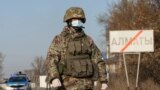 KAZAKHSTAN -- A Kazakh serviceman wearing a protective mask stands guard at a check point, following the state emergency commission's decision to lock down Almaty to prevent the spread of coronavirus disease (COVID-19), on the outskirts of Almaty, Kazakhs