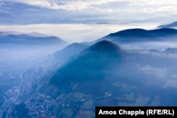 An aerial photo of Visoko and Visocica Hill shot in December. The town is shrouded in smoke from wood-burning fireplaces used for heating.