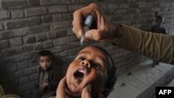 A health worker administers polio vaccine drops to a child during a vaccination campaign in Jalalabad, Afghanistan.