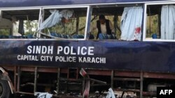 A police officer inspects a damaged police bus at the site of a bomb attack in Karachi on February 13.