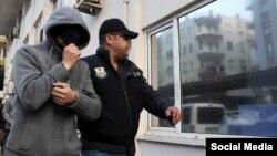 Түрік полицейі содырлар құрамына қосылған Ресей азаматын әкеле жатыр. (Көрнекі сурет)