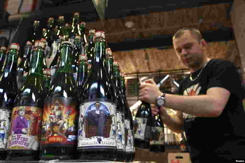 An employee arranges bottles of beer depicting German Chancellor Angela Merkel, Russian President Vladimir Putin, and U.S. President Barack Obama on its labels, at the Pravda Beer Theatre brewery in Lviv, western Ukraine. (Reuters/​Roman Baluk)