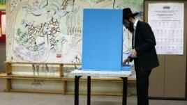 Un evreu ultraortodox votează la o secție electorală din colonia evreiască Kochav Ya'acov, în Cisiordania.