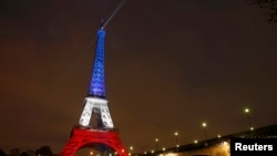 The Eiffel Tower is lit with the blue, white, and red colors of the French flag in Paris on November 16.
