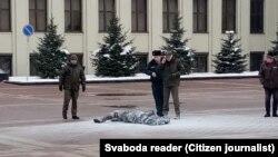 Ходимони полиси Беларус дар назди марде, ки худсӯзӣ кардааст. 22-юми январ, майдони Истиқлолияти Минск