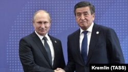 Russian President Vladimir Putin (left) shakes hands with his Kyrgyz counterpart, Sooronbai Jeenbekov, during a welcoming ceremony in Bishkek on November 28.