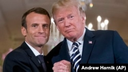 U.S. President Donald Trump (right) and French President Emmanuel Macron embrace at the conclusion of a news conference in the East Room of the White House in Washington, D.C., on April 24.