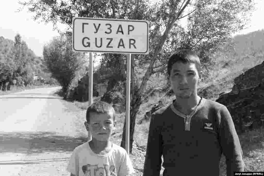 "These children say their village used to be called Dombrachy, Kyrgyz for ""drummer,"" but was renamed Guzar in Tajik. But they also pointed to a sign on the opposite side of the street, where the name Guzar is crossed out, indicating the edge of the village. The children claimed that the sign meant that the village hadn't been renamed after all."