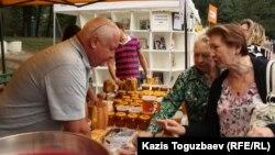 Бал сатушы ер адам жәрмеңкеге шығарған өнімдерін сатып алушыларға ұсынып тұр. Алматы, 16 тамыз 2014 жыл. (Көрнекі сурет)
