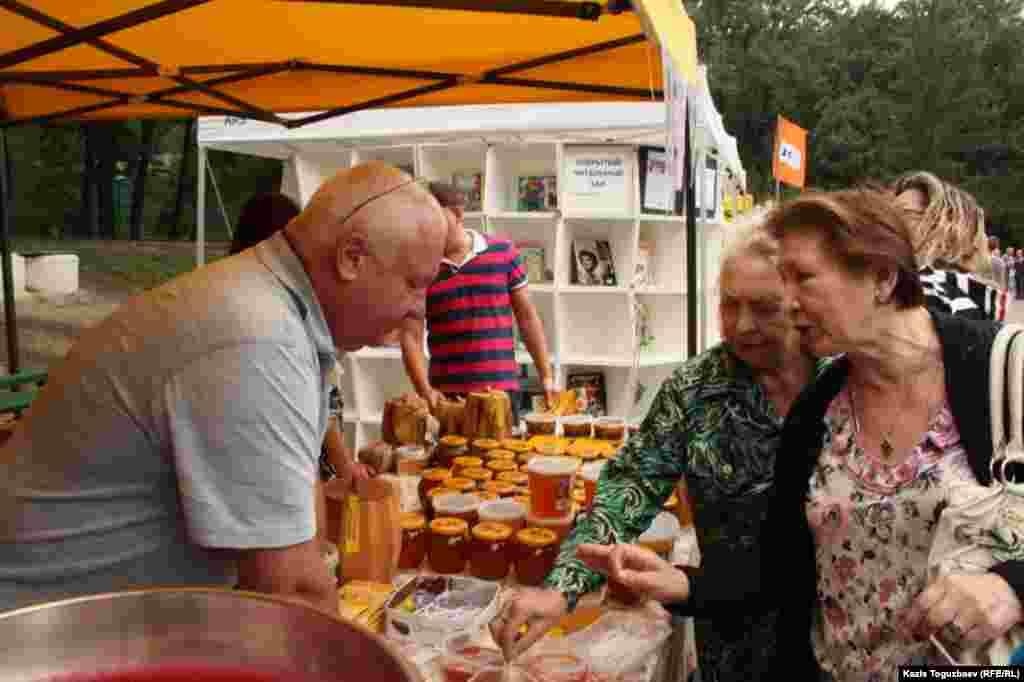 Покупатели пробуют мед на ярмарке.
