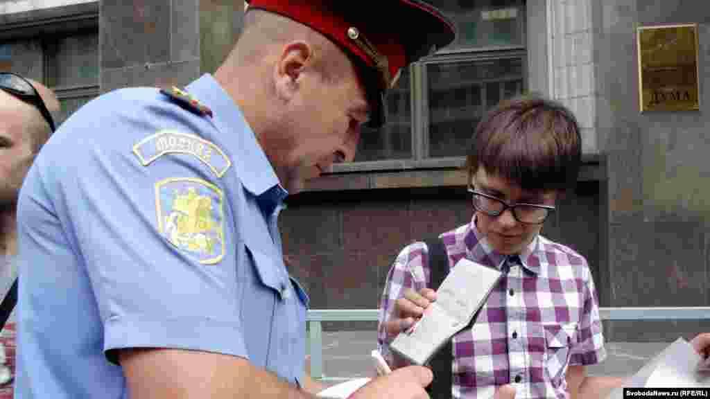 Полицейский переписывает паспортные данные пикетирующего