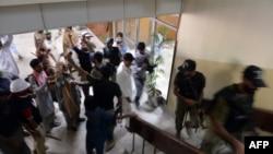 """Пакистанские силы безопасности выводят представителей оппозиции, захвативших телеканал """"Пи-ти-ви"""" из его здания, 1 сентября 2014 года"""