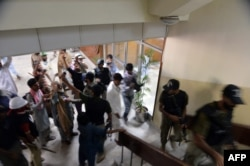 Pakistani security personnel move opposition supporters from the headquarters of the state-owned Pakistani Television in Islamabad on September 1, 2014.