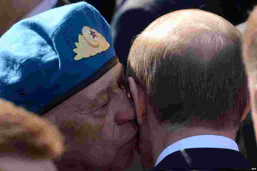 A World War II veteran kisses Russian President Vladimir Putin (right) after the Victory Day parade on Moscow's Red Square.