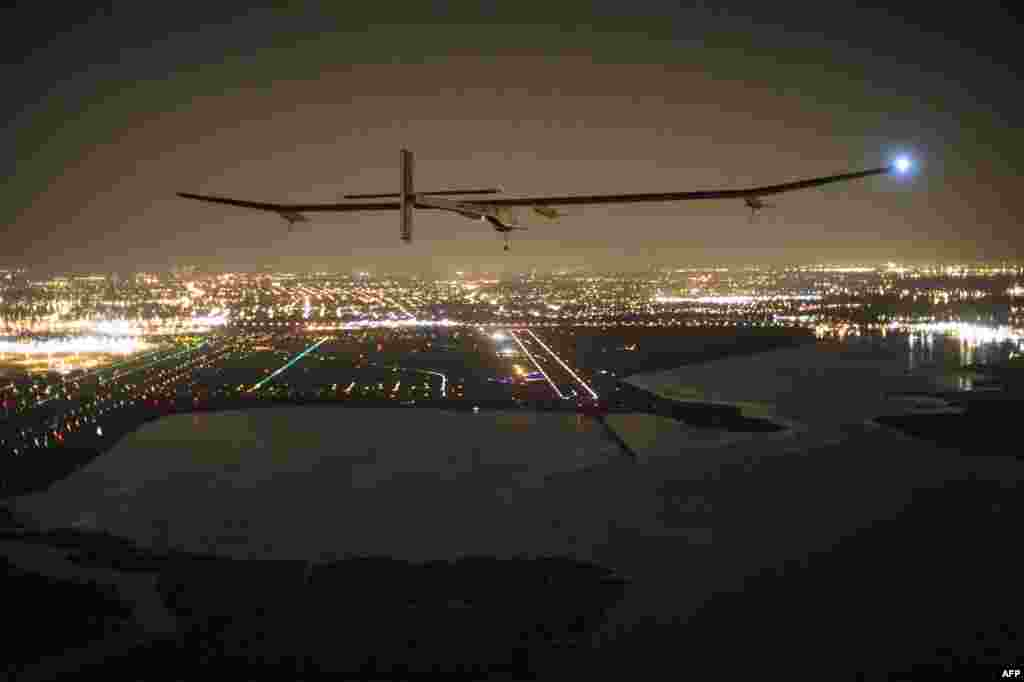 """A handout photo of the """"Solar Impulse HB-SIA"""" aircraft with pilot Andre Borschberg aboard as it approaches its final destination of JFK airport in New York in what Borschberg called a """"huge success for renewable energy."""" (AFP/SolarImpulse/Jean Revillard)"""