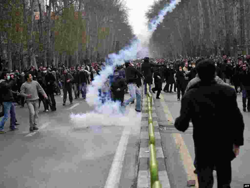 Some of the thousands who reportedly came out to protest in Tehran scatter as a tear-gas canister lands. (AFP)