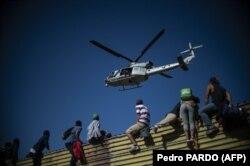 Группа нелегалов перебирается через пограничную стену в США. Тихуана, Мексика, 25 ноября 2018 года