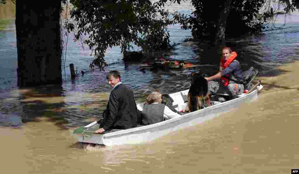 Residents of Gunja, eastern Croatia, ride a boat through flooded streets.