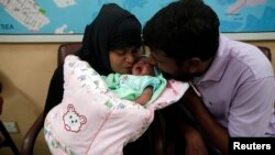 Pakistan -- A childless couple kisses their newly adopted daughter, Fatima, whom Pakistani television talk show host Aamir Liaquat Hussain