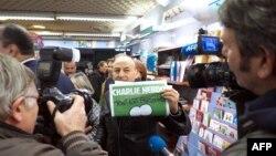 Франциядағы Charlie Hebdo журналының жаңа номерін көрсетіп тұрған адам. Марсель, 14 қаңтар 2015 жыл.