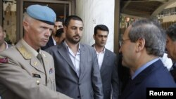 Syria's Deputy Foreign Minister Faisal al-Miqdad (right) greets Major General Robert Mood, chief of the United Nations Supervision Mission in Syria, in Damascus on June 5.