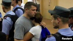 Pyotr Ofitserov embraces his wife after the announcement of the verdict in Kirov on July 18.
