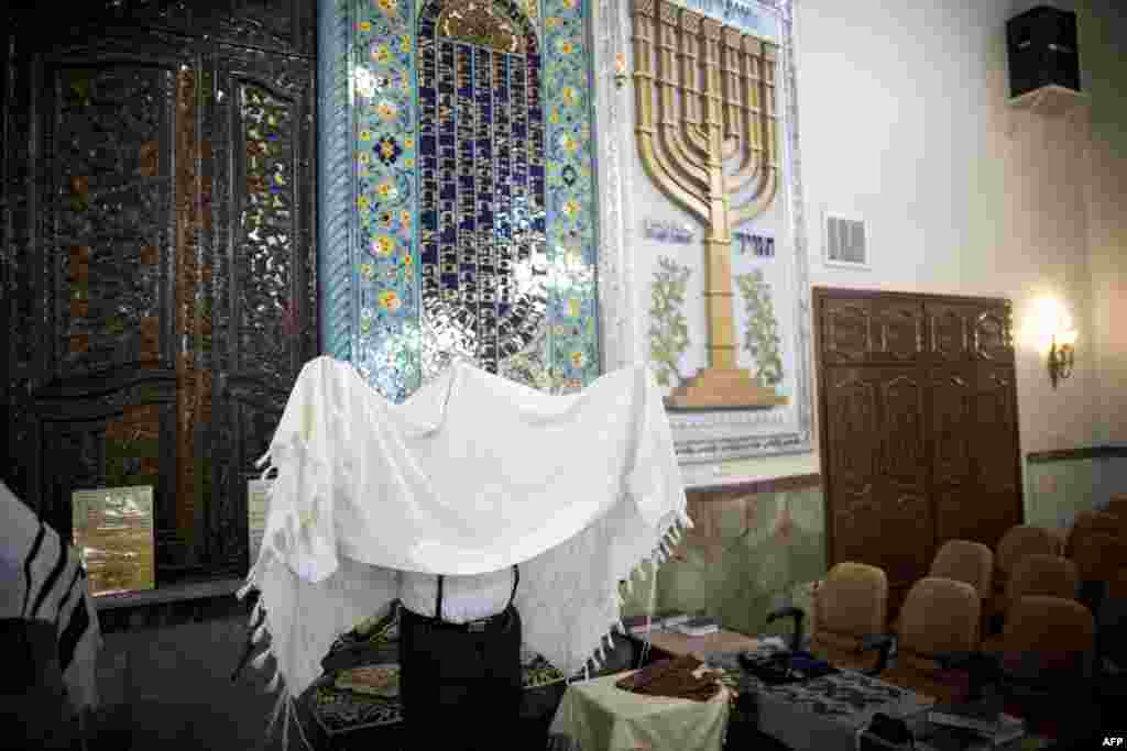 An Iranian Jew wearing a Tallit performs the morning prayer at the Yussef Abad Synagogue.