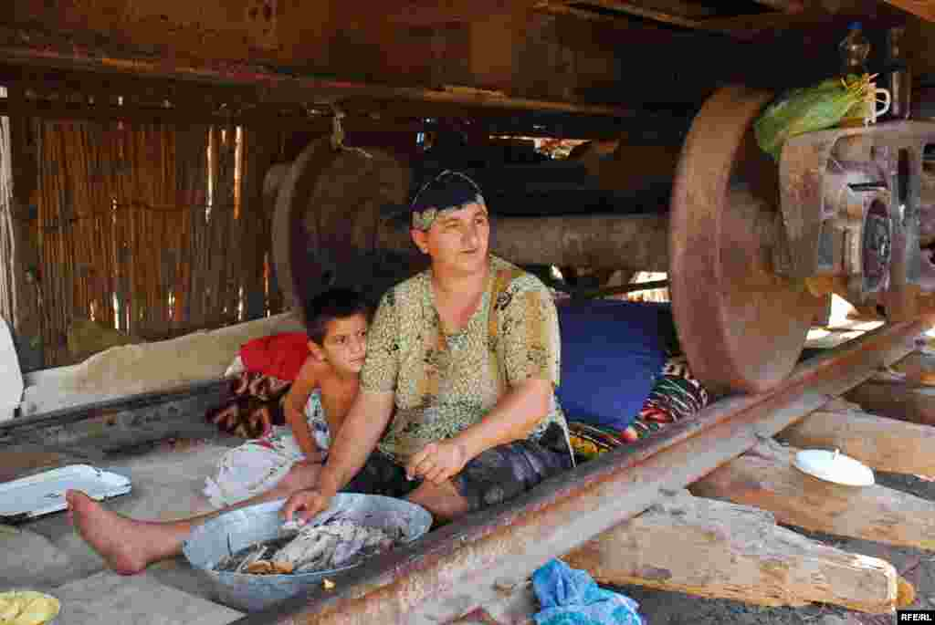 """Azerbaijan - The only place to seek relief from daytime heat is directly underneath the rusting train cars. Baku says it has plans to relocate the Imishli IDPs to a new location. Some oppose the move; others are grimly resigned. """"We live in hell,"""" says Gizbes Asadova. """"If they can return our land, fine. Otherwise they can take us to any hell they want. In the end, it doesn't matter. Either we die here or we die there."""""""