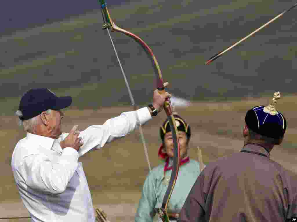 U.S. Vice President Joe Biden (left) fires an arrow while on a tour at a Mini Nadam, or Mongolian wrestling performance, in Ulan Bator on August 22. Photo by Andy Wong for AP