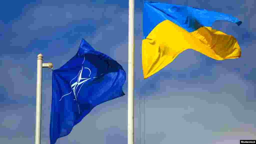 Національний прапор України поруч із прапором Організації Північноатлантичного договору(НАТО) під час церемонії відкриття міжнародних навчань рятувальних служб«Україна-2015», у яких беруть участь держави-члени НАТО та партнери альянсу. 21 вересня 2015 року