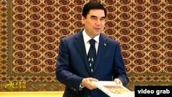 Türkmenistanyň prezidenti Gurbanguly Berdimuhamedow we onuň çaý barada ýazandygy aýdylýan kitaby.
