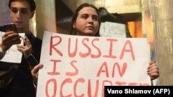 Девушка с плакатом «Россия — оккупант» у здания парламента Грузии. 20 июня 2019 года.