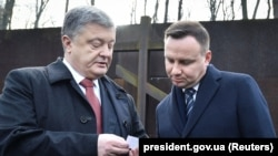 Polish President Andrzej Duda (right) talks with Ukrainian President Petro Poroshenko during a visit to the memorial for the victims of totalitarianism in Kharkiv, Ukraine, in December 2017.