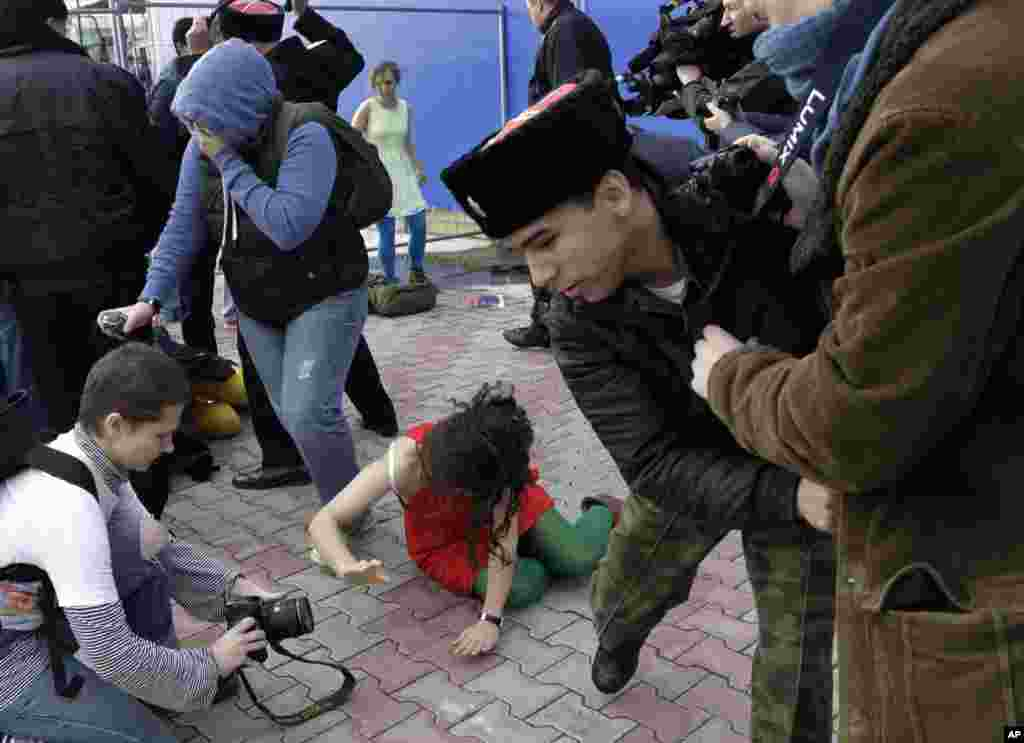 A member of Pussy Riot lies on the ground as the group are attacked by Cossack militia.