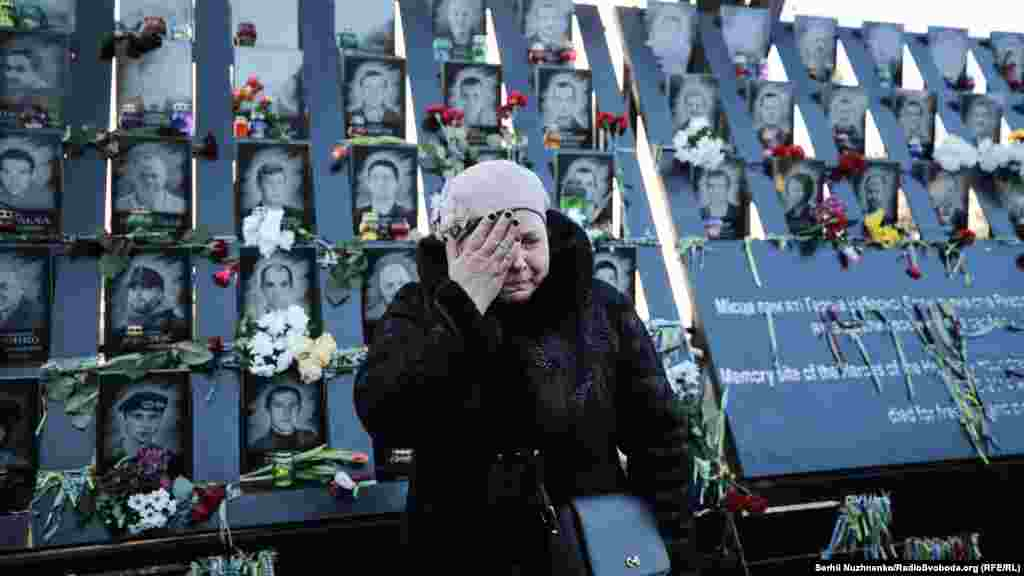 A woman stands before a memorial to those killed in the 2014 Euromaidan uprising on the Alley of the Heroes of the Heavenly Hundred in Kyiv, Ukraine, on February 18. (Serhii Nuzhnenko, RFE/RL)