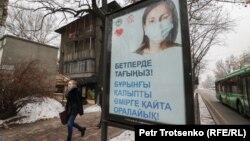 Прохожая в Алматы возле баннера с призывом носить защитную маску во время пандемии.