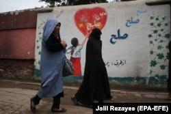 Афганские женщины проходят мимо стены с надписью: «Мир» — в Герате, 3 мая 2021 года